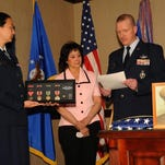 Col. Robert Stanley, 341st Missile Wing commander, reads a citation to Anna Gilmore, center, which outlines her father's service and earned medals, as Capt. Jessica Tiffany, 341st MW executive officer, holds a display with all the medals in it during a small ceremony in Stanley's office March 11.
