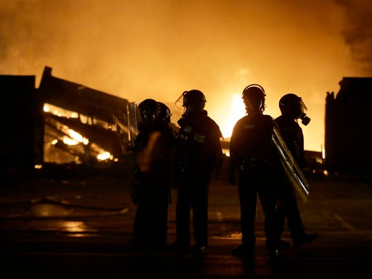 Police officers watch the neighborhood as some buildings are set on fire Monday night.