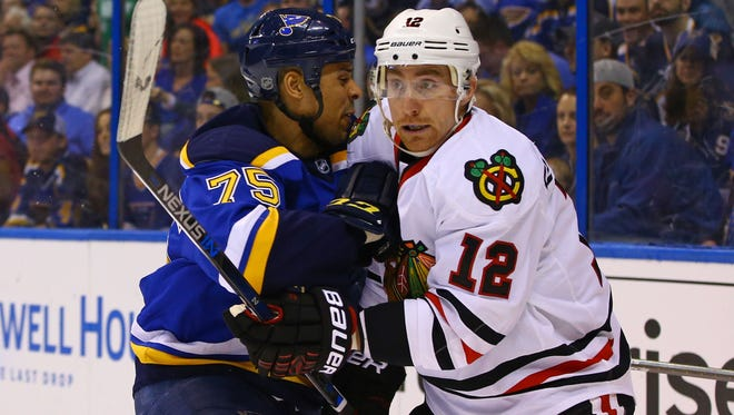 Chicago Blackhawks left wing Tomas Fleischmann (12) is checked by St. Louis Blues right wing Ryan Reaves (75) during the second period in Game 2 of their first-round series.
