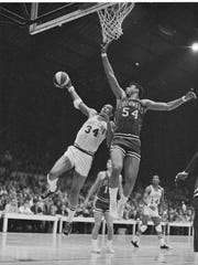 Mel Daniels (34) of the Indiana Pacers stretches past Gene Moore (54) of the Kentucky Colonels for 2 points during the first game of their ABA playoffs in Indianapolis, Ind., April 9, 1969.  Daniels scored 18 points and Moore 19 as the Colonels won, 128-118.  (AP Photo)