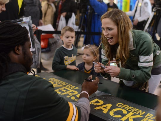 De Pere resident Abby Rubens reacts as Green Bay Packers running back Eddie Lacy (27) say yes to using her silver pen to sign her Packers memorabilia at the Salvation Army's Big Red Kettle in Bay Park Square mall on Monday in Ashwaubenon.