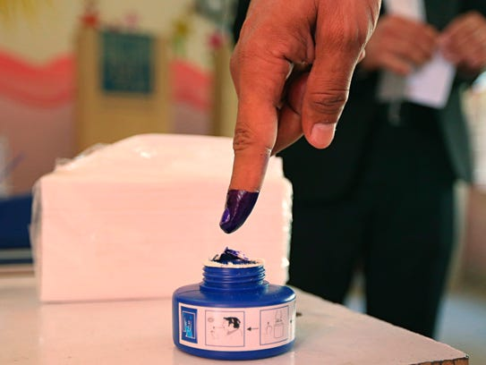 An Iraqi soldier dips his finger in ink after voting
