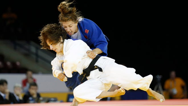 Marti Malloy of the United States (white) competes against Catherine Beauchemin-Pinard of Canada (blue) in the women's 57-kilogram judo gold medal contest during the 2015 Pan Am Games at Mississauga Sports Centre.