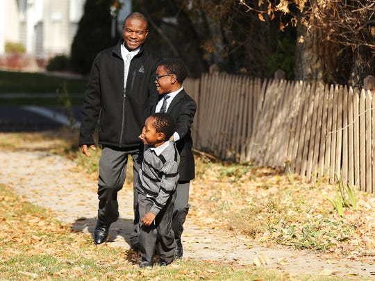 Joseph Genda walks with his sons Norman, 10, and Patrick, 4, near their home in Salt Lake City on Sunday, Nov. 18, 2018.