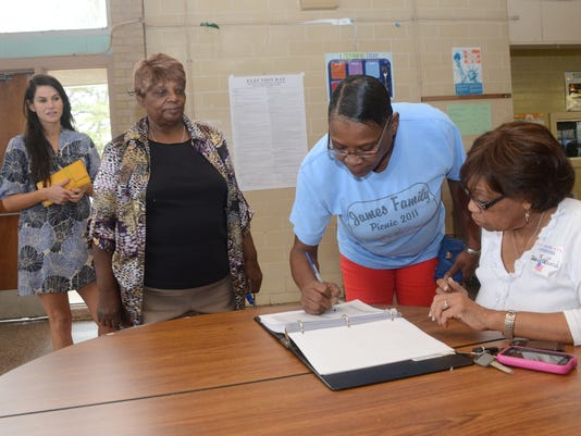 ANI Voting Polling commissioner Jean Bradford (far right) watches as Denise Bush signs the poll book Saturday, Dec. 6, 2014 at Precinct 28 at Alexandria Middle Magnet School. Waiting in line to vote are Arthurlene West (second from left) and Amelie Freedma