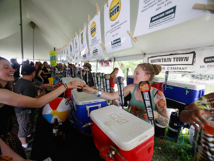 Heather Pillsbury, of Lansing, pours a beer from one