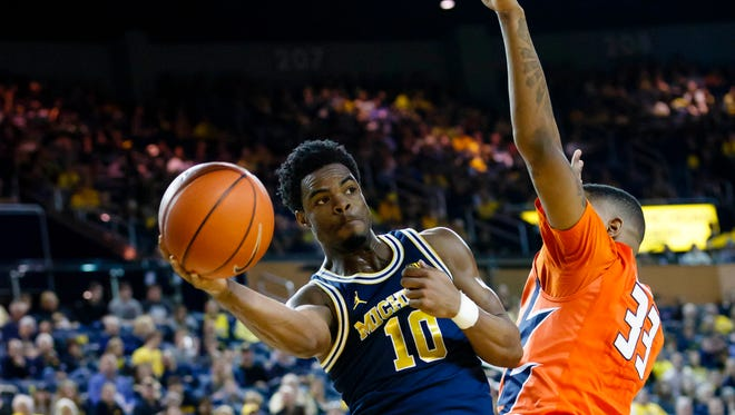 Michigan guard Derrick Walton Jr. (10) passes defended by Illinois center Mike Thorne Jr. (33) in the first half of Michigan's 66-57 win Saturday at Crisler Center.
