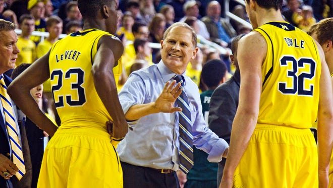 Michigan head coach John Beilein, center, gives instructions to guard Caris LeVert (23) and forward Ricky Doyle (32) during a timeout in the second half of an NCAA college basketball game against Eastern Michigan at Crisler Center in Ann Arbor, Mich., Tuesday, Dec. 9, 2014. Eastern Michigan won 45-42.