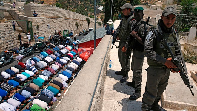 Israeli security forces stand guard as Palestinian Muslim worshippers pray outside Lions Gate, a main entrance to the Al-Aqsa mosque compound in Jerusalem's Old City, on Thursday, n protest against new Israeli security measures implemented at the holy site.