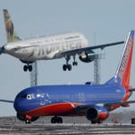 A Southwest Airlines plane waits to take off as a Frontier Airlines plane lands at Denver International Airport on Feb. 8, 2016.