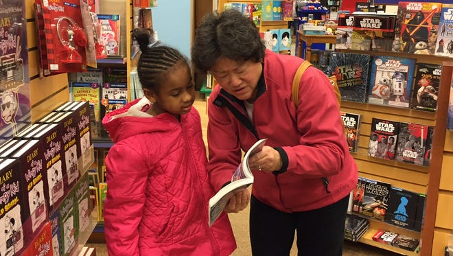 """Pauline Shen looks at a book with a student last December during a program with """"Heads Up,"""" an initiative Shen started to help mentor local youth. Shen is one of the honorees selected for the 2016 Salute to Women awards."""