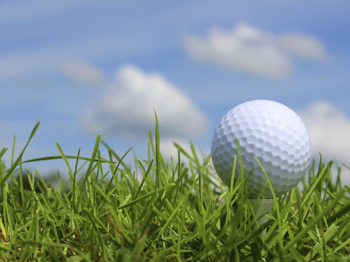 Close-up golf ball in grass on golf course, blue sky