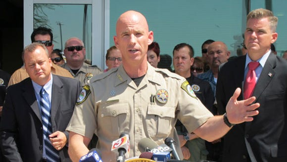 Pinal County Sheriff Paul Babeu, flanked by attorney