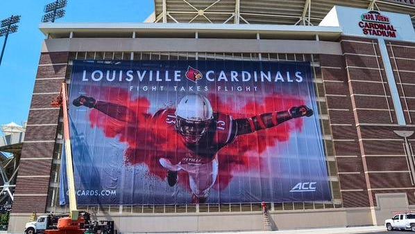 Photo of banner featuring James Burgess outside Papa John's Cardinal Stadium.