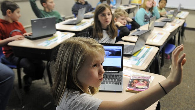 Kayla Weidenaar raises her hand to ask a question about the Google classroom setup during Jen Albig's fourth- and fifth-grade class Monday at Jefferson Elementary School in Sioux Falls.