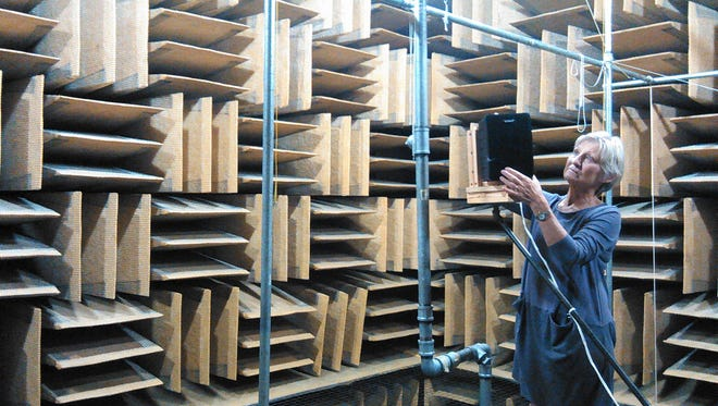 Large fiberglass wedges serving as sound-stifling baffles protrude inward from all six surfaces of this carefully-designed anechoic chamber at the University of Iowa, one of the first in the country when built in 1968.  Professor Ruth Bentler, shown here examining a speaker used in a research project, calls this room an invaluable tool for research on hearing aid effectiveness.