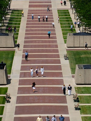 State workers and others walk on the pedestrian mall area between the Hall of Justice and the state Capitol building in Lansing just in this 2007 State Journal file photo.