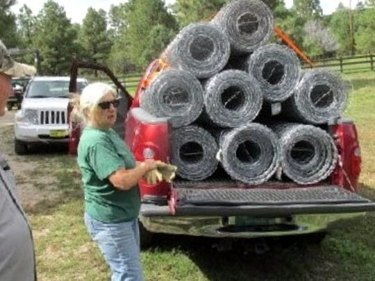A volunteer arrives with rolls of fencing to be added.