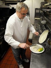 Michael's head chef Randy Meyer prepares a schnitzel dish Friday at the restaurant in St. Cloud.