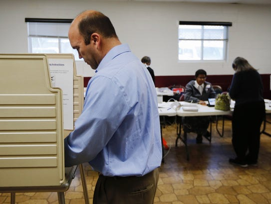 Tom Craft, of Oakley, fills out his ballot at the Madison