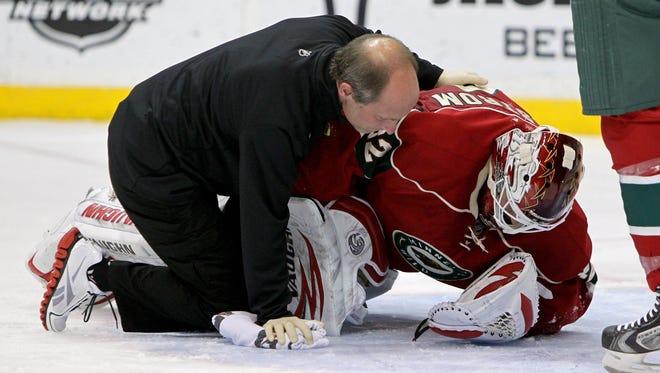 Minnesota Wild goalie Niklas Backstrom is examined by a trainer after he was hit by Toronto's Nazem Kadri.