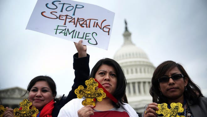"""Natividad Gonzalez, center, of Clanton, Ala., and other immigration reform activists holds signs and """"Badges of Courage"""" during a news conference at the east front of the U.S. Capitol, Tuesday."""