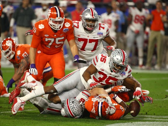 Ohio State Buckeyes defensive end Sam Hubbard (6) and  Ohio State Buckeyes linebacker Chris Worley (35) tackle  Clemson Tigers running back Wayne Gallman (9) during the first quarter of the College Football Playoff Semifinal game in the PlayStation Fiesta Bowl on Dec. 31, 2016 at University of Phoenix Stadium in Glendale, Arizona.