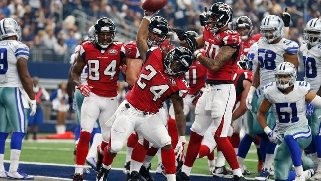 Atlanta Falcons running back Devonta Freeman looks to spike the Cowboys.