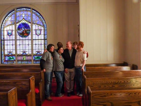 Rev. Kurt Stutler, middle, talks with homeless at South