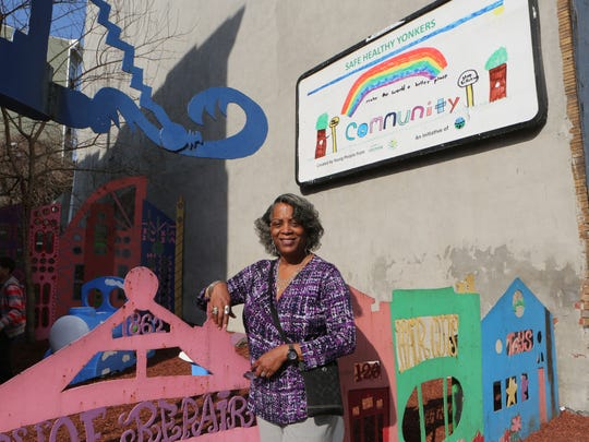 """Theresa Colyar, the Community Service Coordinator for Westhab, is pictured in front of one of their new """"Safe Healthy Yonkers"""" billboards along Elm Street in Yonkers."""
