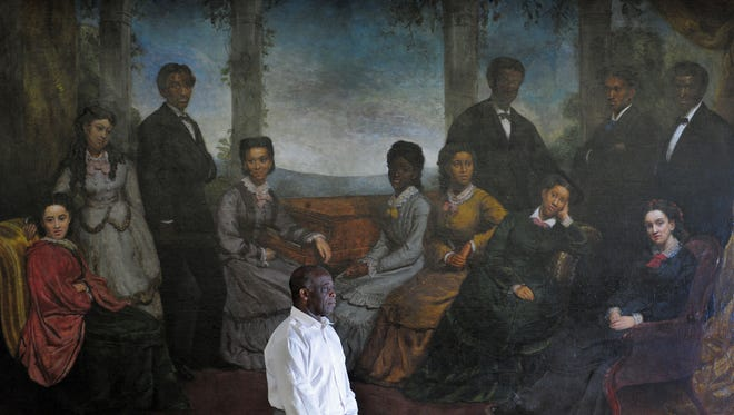 Dr. Paul Kwami, musical director for the Fisk Jubilee Singers, stands in front of a painting of the original Fisk Jubilee Singers which dates back to the late 19th century.
