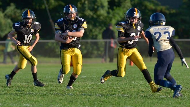 During one of four homecoming games Sept. 24, the Plymouth-Canton Steelers come strong on this running play.