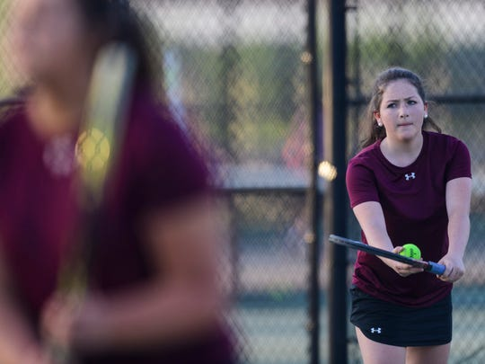 Henderson County's Isabelle Wright (back) prepares to serves up the ball as she takes on a Madisonville pair with her teammate Kally Priest Second Region girls doubles semifinal match against Madisonville at the Doc Hosbach Tennis Complex in Henderson, Ky., Tuesday, May 8, 2018. The pair lost in a tiebreaker trifecta to Madisonville's Emily Shockley and Emily Fischels 7-6, 6-7, 10-3.