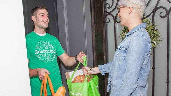 An Instacart employee makes a grocery delivery to a customer.