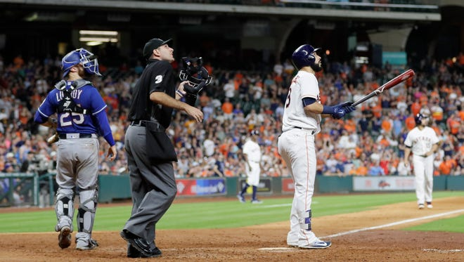 Houston Astros' Marwin Gonzalez, right, watches his grand slam along with home plate umpire Pat Hoberg, center, and Texas Rangers catcher Jonathan Lucroy (25) during the eighth inning of a baseball game, Tuesday.