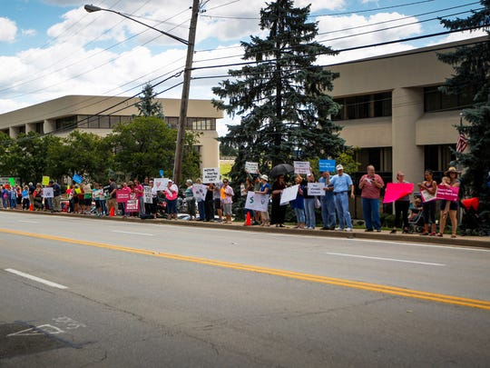 Nearly 100 people line Dixie Highway in front of U.S. Senator Mitch McConnell's offices in Northern Kentucky Monday, June 26, 2017.