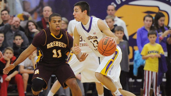 Christian Munson of Guerin works the ball around Brebeuf defender P J Thompson. Guerin hosted Brebeuf in basketball January 24, 2014.