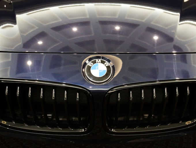 Exhibition hall lights gleam off a BMW hood as visitors