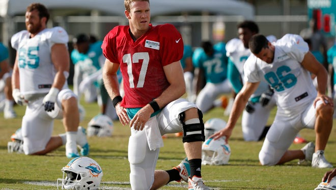Miami Dolphins quarterback Ryan Tannehill stretches out during an NFL football training camp, Thursday at the Dolphins training facility in Davie. During the practice session, Tannehill reinjured his left knee. The extent of the injury is not known.