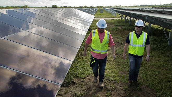 FPL's construction manager Gary Newton and public affairs specialist Stephen Heiman look over newly installed solar panels at FPL's Hibiscus Solar Energy Center that sits on 400 acres of land on Westlake's west side October 23, 2019. Two thousand five hundred panels of the 300,000 have been installed. Palm Beach County?s first large utility-scale solar plant should be online in 2020. Each solar panel, which were made in Ohio, creates 425 watts of electricity. The solar plant will generate zero-emissions electricity for FPL customers ? enough to power approximately 15,000 Florida homes and equivalent to removing approximately 12,000 cars from the road each year. [ALLEN EYESTONE/palmbeachpost.com]