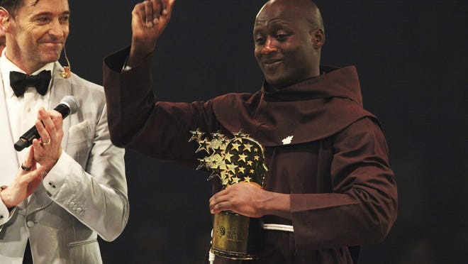 Kenyan teacher Peter Tabichi, right, reacts near actor Hugh Jackman, after winning the $1 million Global Teacher Prize in Dubai, United Arab Emirates, Sunday, March 24, 2019. Tabichi is a science teacher who gives away 80 percent of his income to the poor in the remote Kenyan village of Pwani.