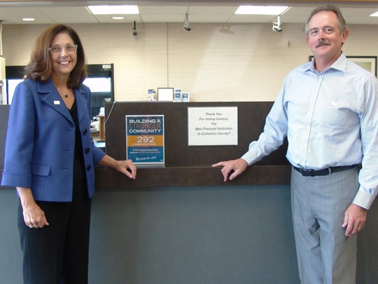 Beccy Porteus and Bob Bigrigg pose by the counter at Century National Bank at 100 Downtowner Plaza in Coshocton.