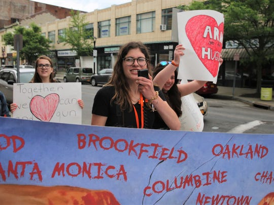 Emmie Magliato, 17, of the Town of Poughkeepsie, leads a chant on Sunday. She was one of the students calling for stricter gun laws in marching through the City of Poughkeepsie.