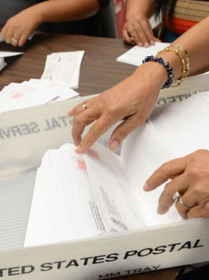 In this March 2013 file photo, Department of Administration staff prepare income tax refund checks for mailing. More than $1 million in refunds will be sent out Friday.