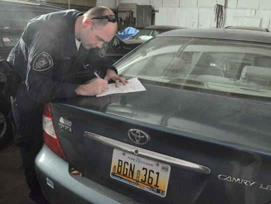 Battle Creek Officer Andrew Olsen completes the paperwork