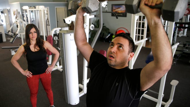 Personal trainer Maria Munoz watches Ricardo Arguello's form Thursday while he does a set of shoulder presses at Personal Fitness Trainers and Wellness Studio in Appleton.