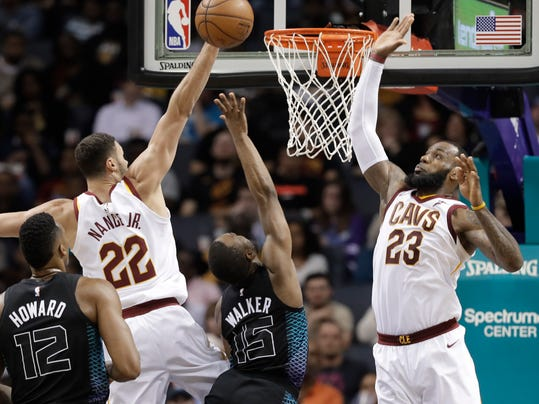 Charlotte Hornets' Kemba Walker (15) shoots between Cleveland Cavaliers' LeBron James (23) and Larry Nance Jr. (22) during the second half of an NBA basketball game in Charlotte, N.C., Wednesday, March 28, 2018. (AP Photo/Chuck Burton)