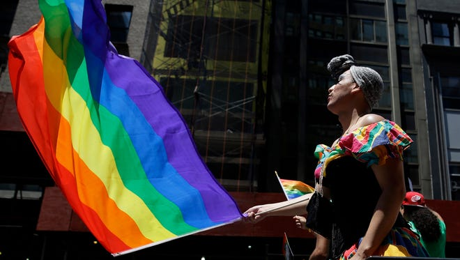 People on a float dance and wave flags during the Gay Pride Parade in New York. Fifth Avenue became one big rainbow on Sunday, as thousands of participants waving multicolored flags made their way down the street for New York City's annual Gay Pride march.