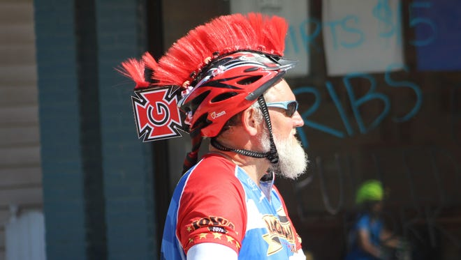 Grinnell College alumnus Robert Meyer, of Miami, Fla., comes through Montezuma with a decorated bike helmet that includes a Pioneers logo.