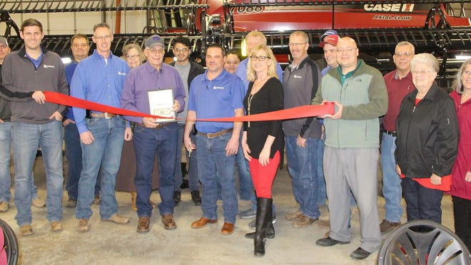 Rodney Walker, Pratt manager for KanEquip, (center with scissors) along with members of his staff and members of the Pratt Area Chamber of Commerce, gather to cut a dedication ribbon as part of a customer appreciation event on Feb. 27 at their facility on East First Street in Pratt. Chamber members at the event included Executive Director Kim DeClue (next to Walker on right), President Elect Mark Ploger (with presentation frame) and Chamber President Kelley Simon (holding ribbon at right).